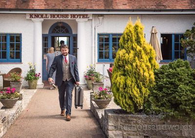Groom in blue suit and grey tweed waistcoat smiling as he leaves Knoll House Hotel on Dorset wedding morning