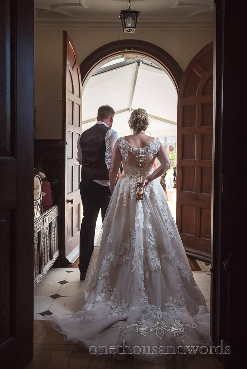 Groom leads bride through wooden doorway in to wedding marquee with beer hidden behind her back