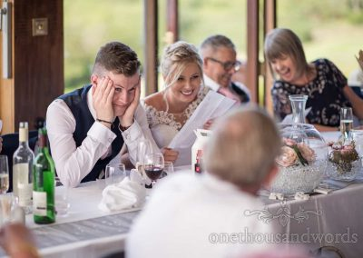 Groom at the top table looks embarrassed by best man's picture given out to laughing guests during wedding speeches