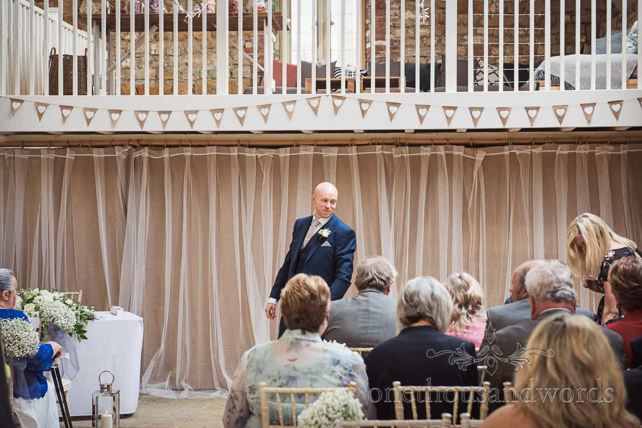 Groom in blue suit looking at wedding guests as he waits for Bride's arrival in front of curtains under hessian and love heart bunting