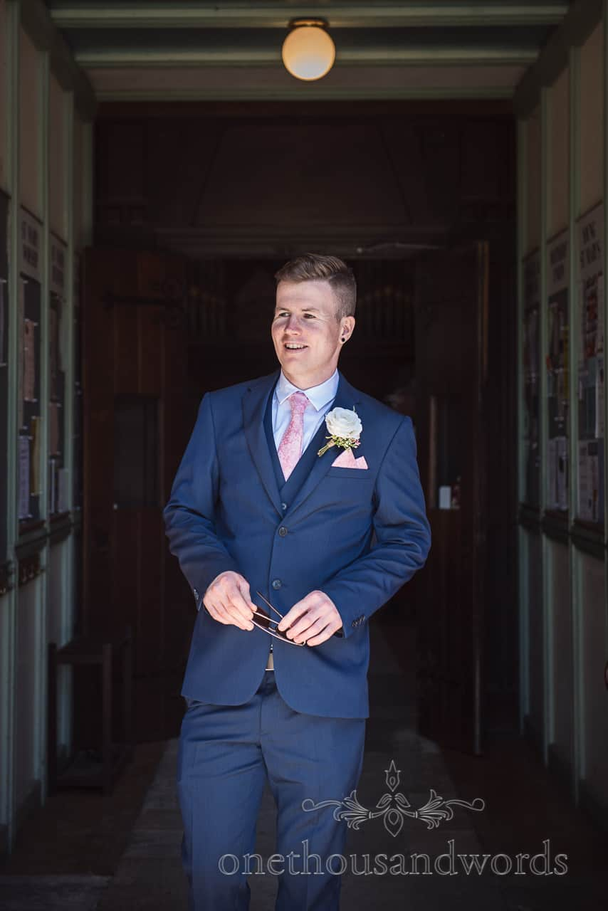 Smiling groom waits outside church wedding venue doorway wearing a three piece blue wedding suit in the summer sunshine