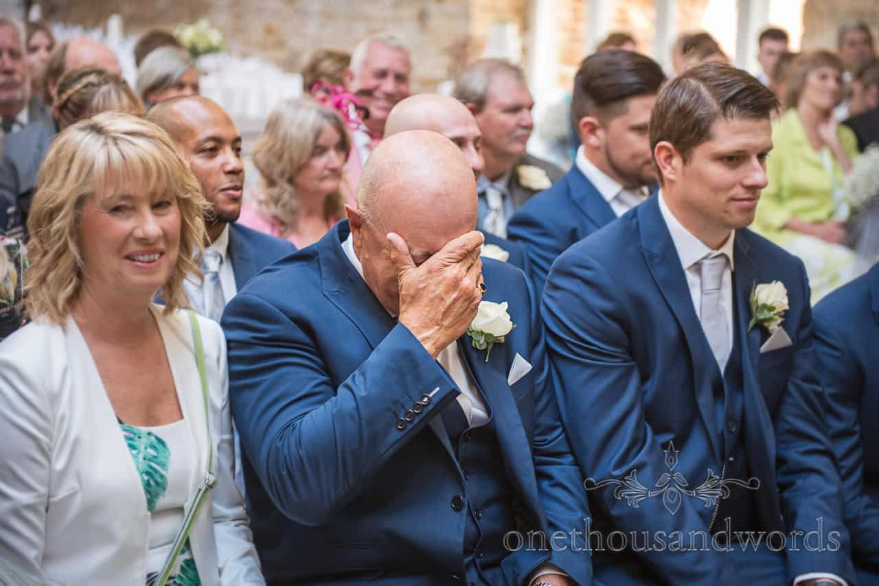 Emotional groom's father in blue suit cries with his head in his hands during Tithe Barn wedding ceremony in Dorset