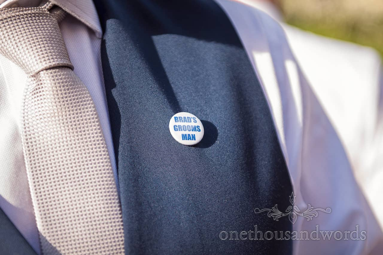 Brad's Grooms Man pin badge worn on blue wedding waistcoat with grey and silver patterned tie. Wedding detail photograph