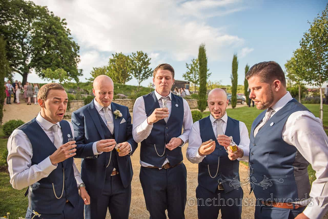 Grooms men wearing blue wedding suits drink Tequila shots together reaction photograph in wedding venue gardens