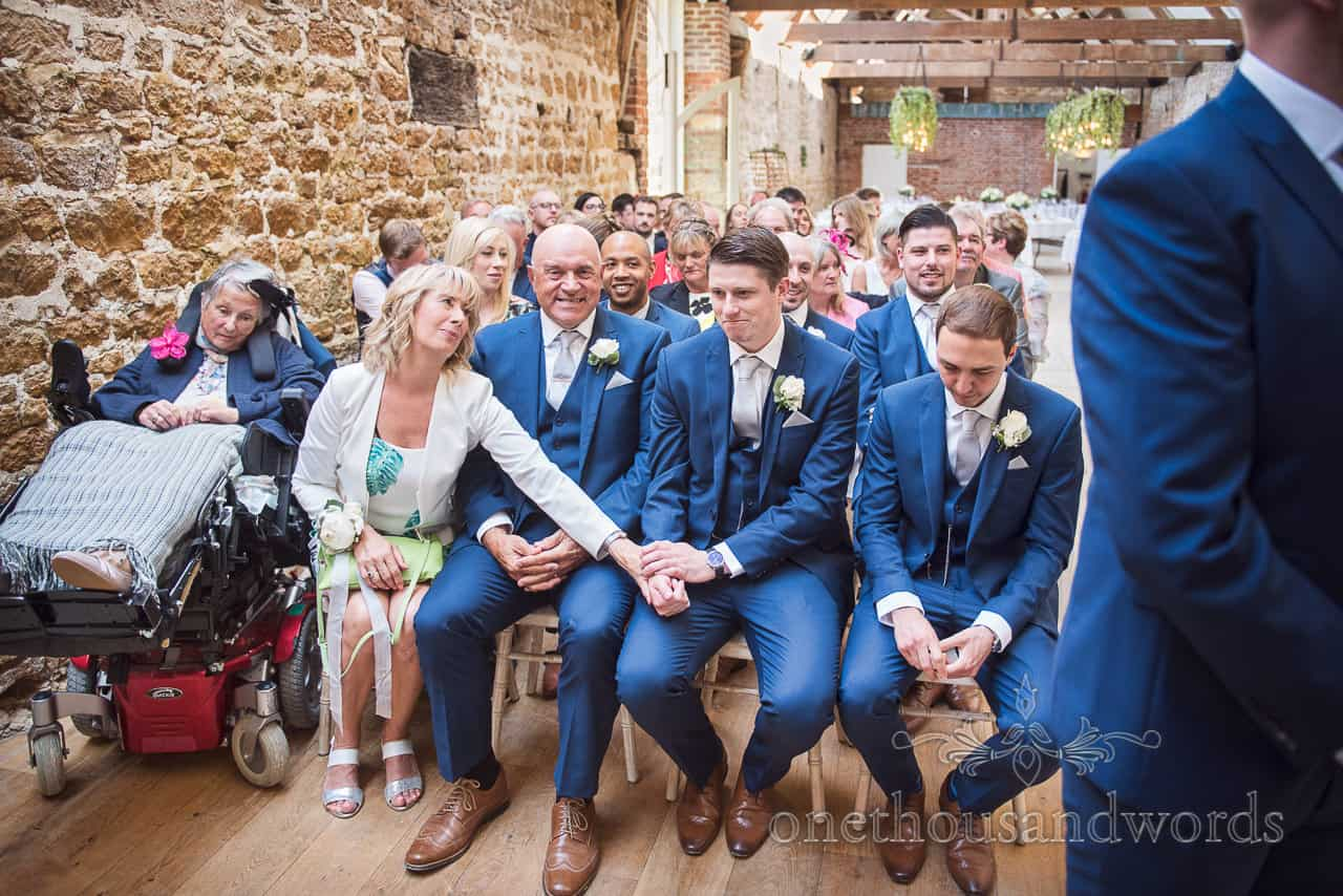Groom's mother comforts best man in blue suit before Dorset stone barn wedding ceremony as they wait for the bride's arrival