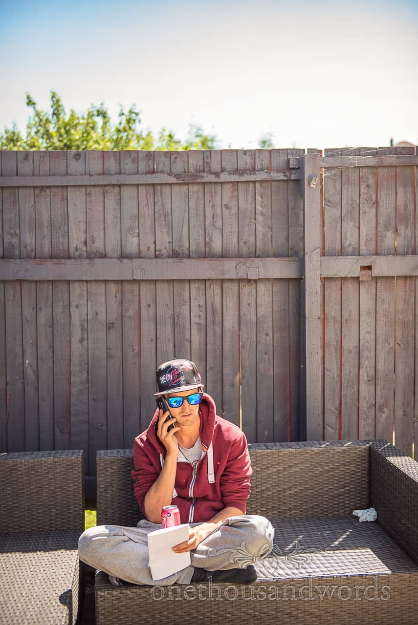 Groomsman speaks on mobile phone sat in the sun in the garden wearing a tracksuit, sun cap and sun glasses before changing