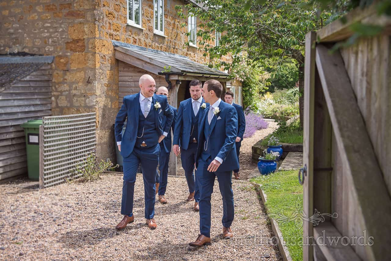 Groomsmen walk in brown shoes and blue suits at Crepe Cottage on the Symondsbury Estate, Dorset on wedding morning