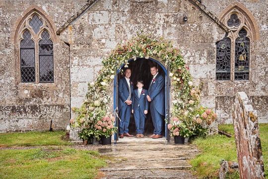 Groom and groomsmen shelter from rain at church at the same time as bridal preparations