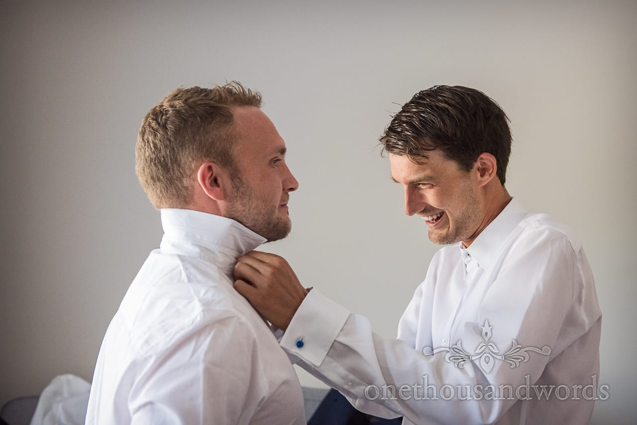 Happy groomsmen in white shirts dress each other during natural wedding morning preparation photographs