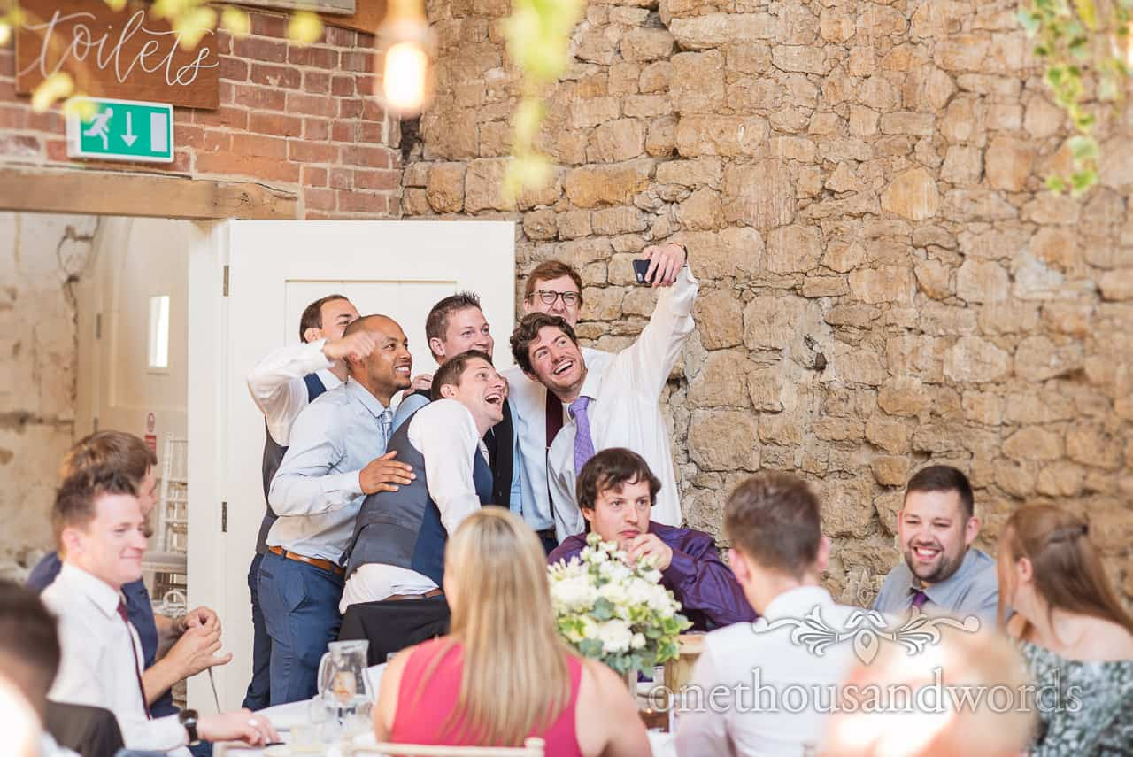 Happy group of male wedding guests take a selfie during a stone barn wedding breakfast next to toilet door