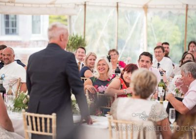 Wedding guests happy reaction during father of the bride's wedding speech in marquee venue