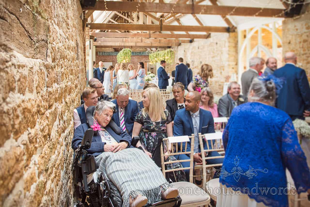 Wedding guests and granny in a wheelchair take their places either side of the aisle at the Tithe Barn Dorset wedding venue