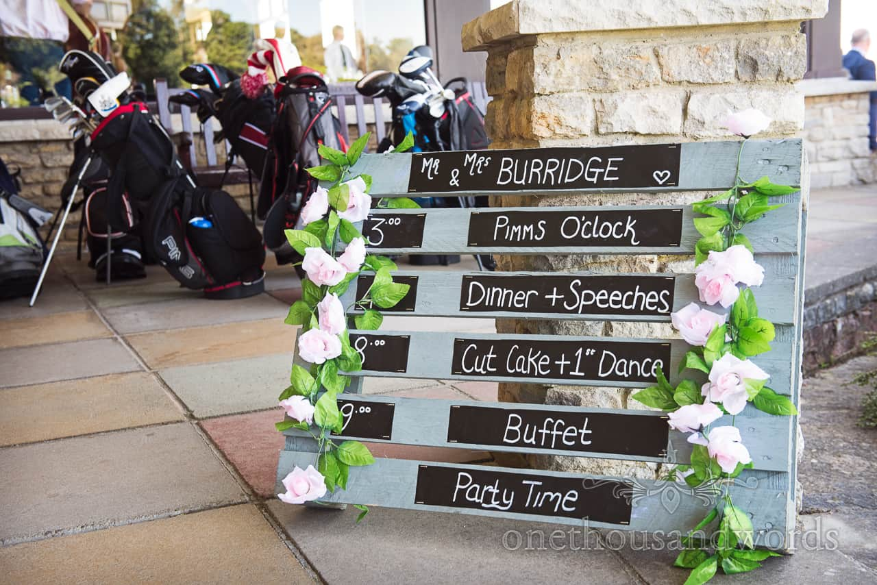 Hand made sky blue painted and decorated wooden pallet wedding running order of the day with white flowers idea