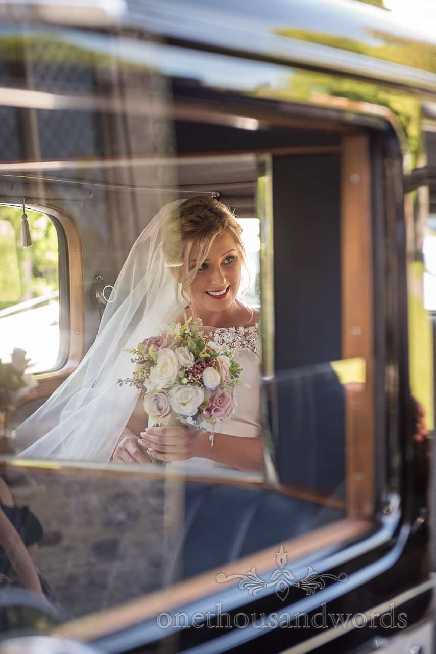Happy blonde bride smiling with veil in the back of a classic wedding car holding a pastel flowers wedding bouquet