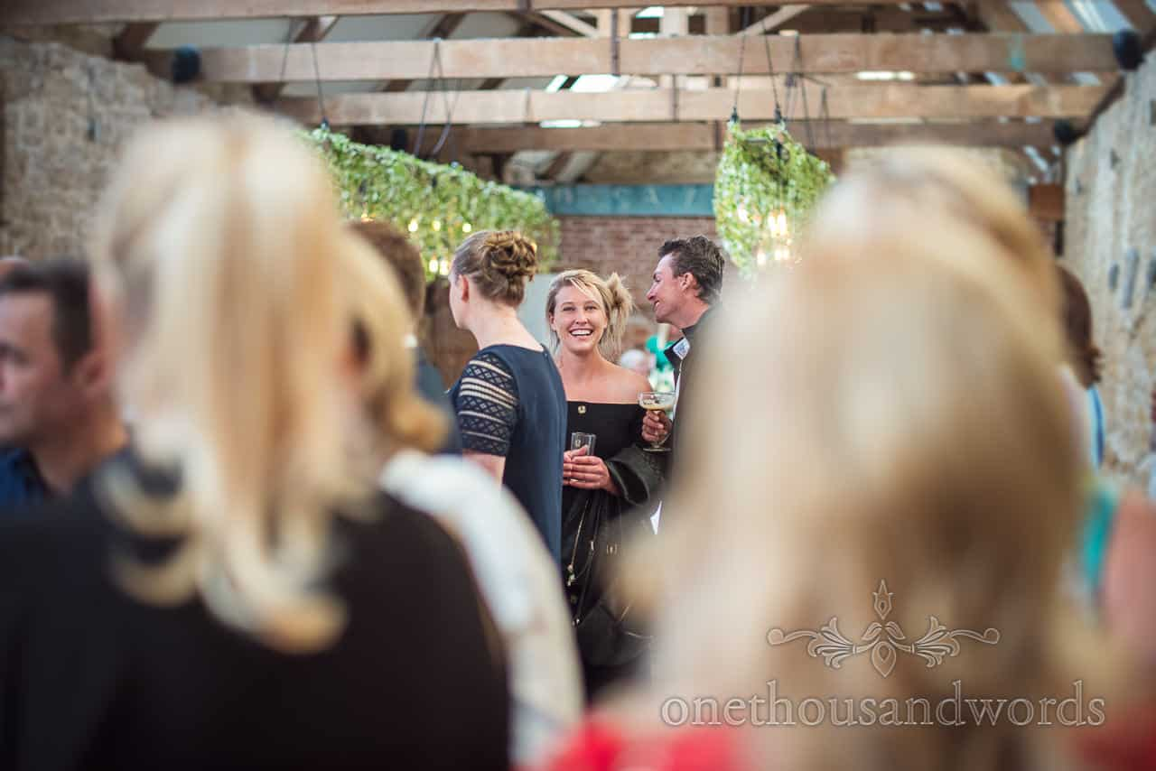 Happy blonde wedding evening guest in barn venue smiling within crowd of other wedding guests