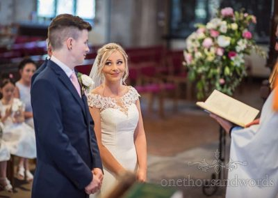 Happy bride and groom look into each others eyes during their Dorset church wedding ceremony conducted by vicar