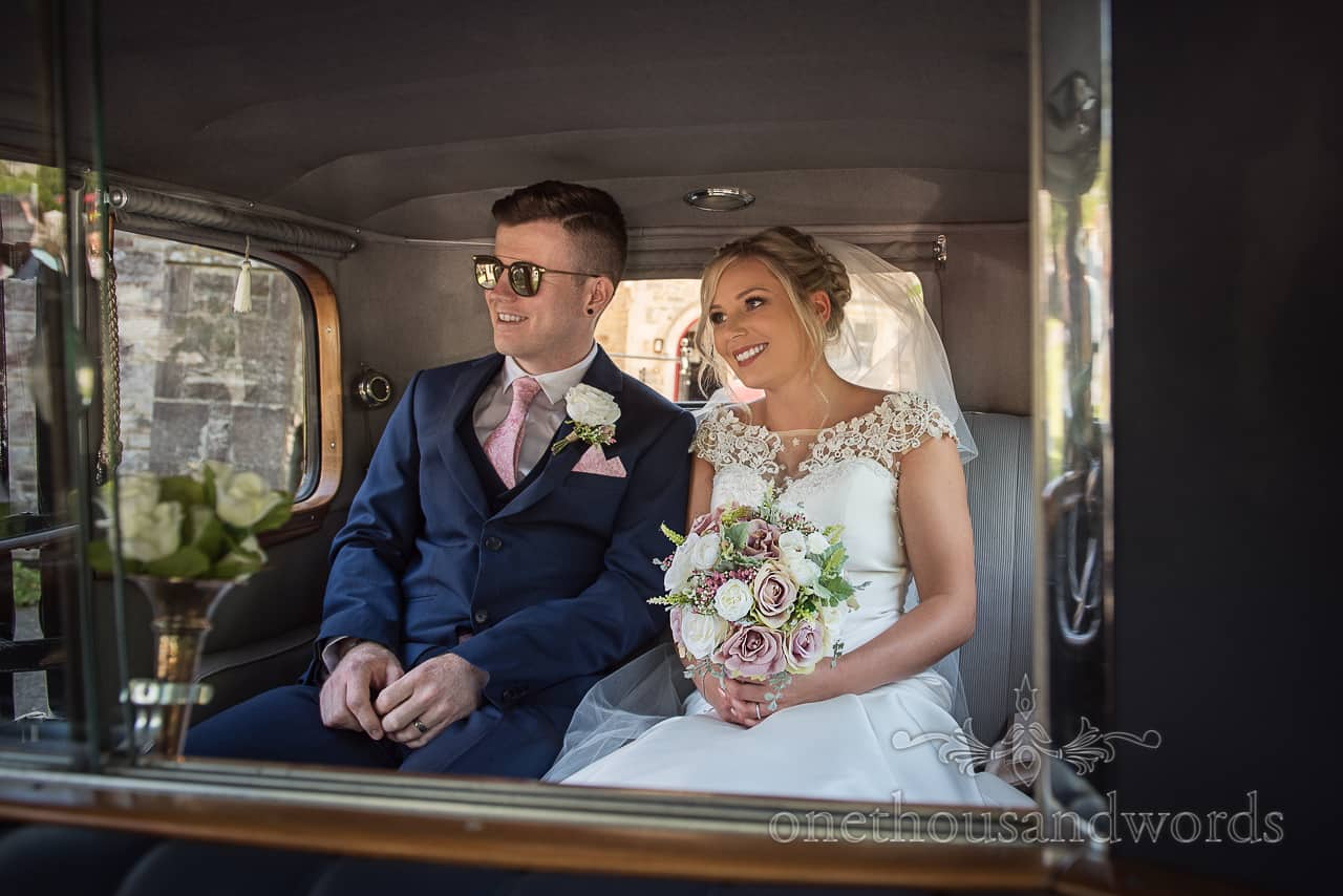Happy bride and groom are passengers in the back seats of a classic wedding car transport photograph