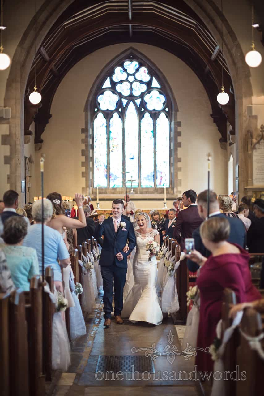 Happy bride and groom walk down the aisle after their Dorset church wedding ceremony groom gives high five to wedding guest