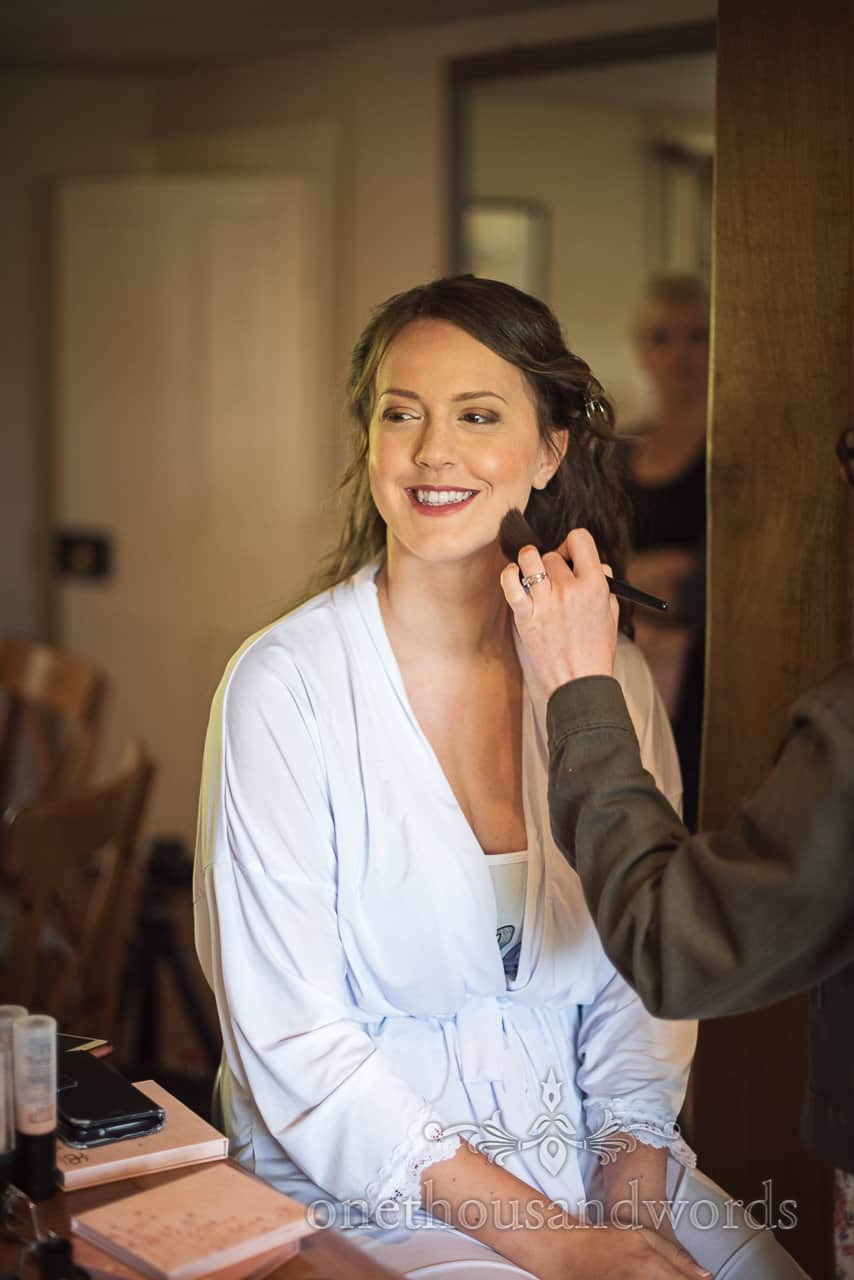 Happy bride on wedding morning having bridal make up styled by professional wedding makeup artist in Dorset