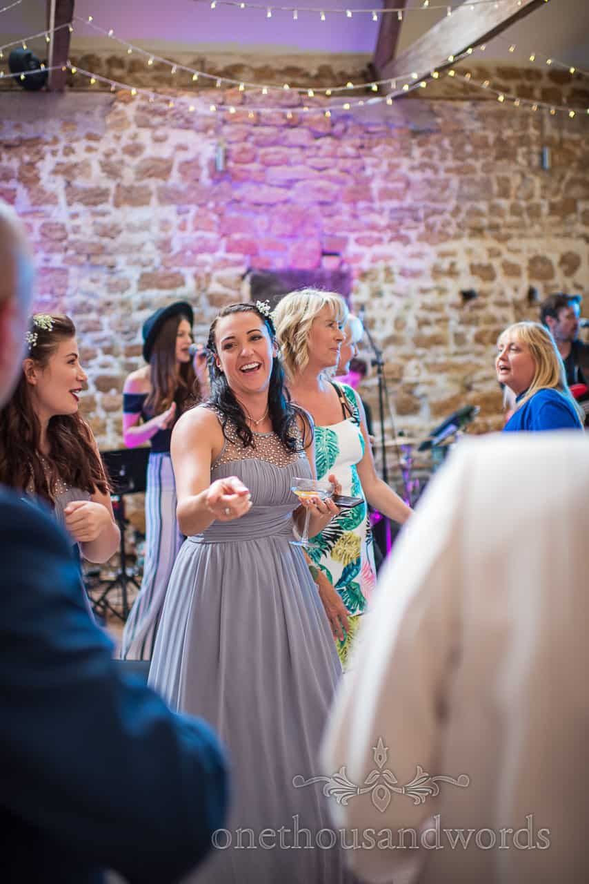 Happy Bridesmaid Wearing Pastel Blue Dress Dancing With Drink In Hand Documentary Photograph