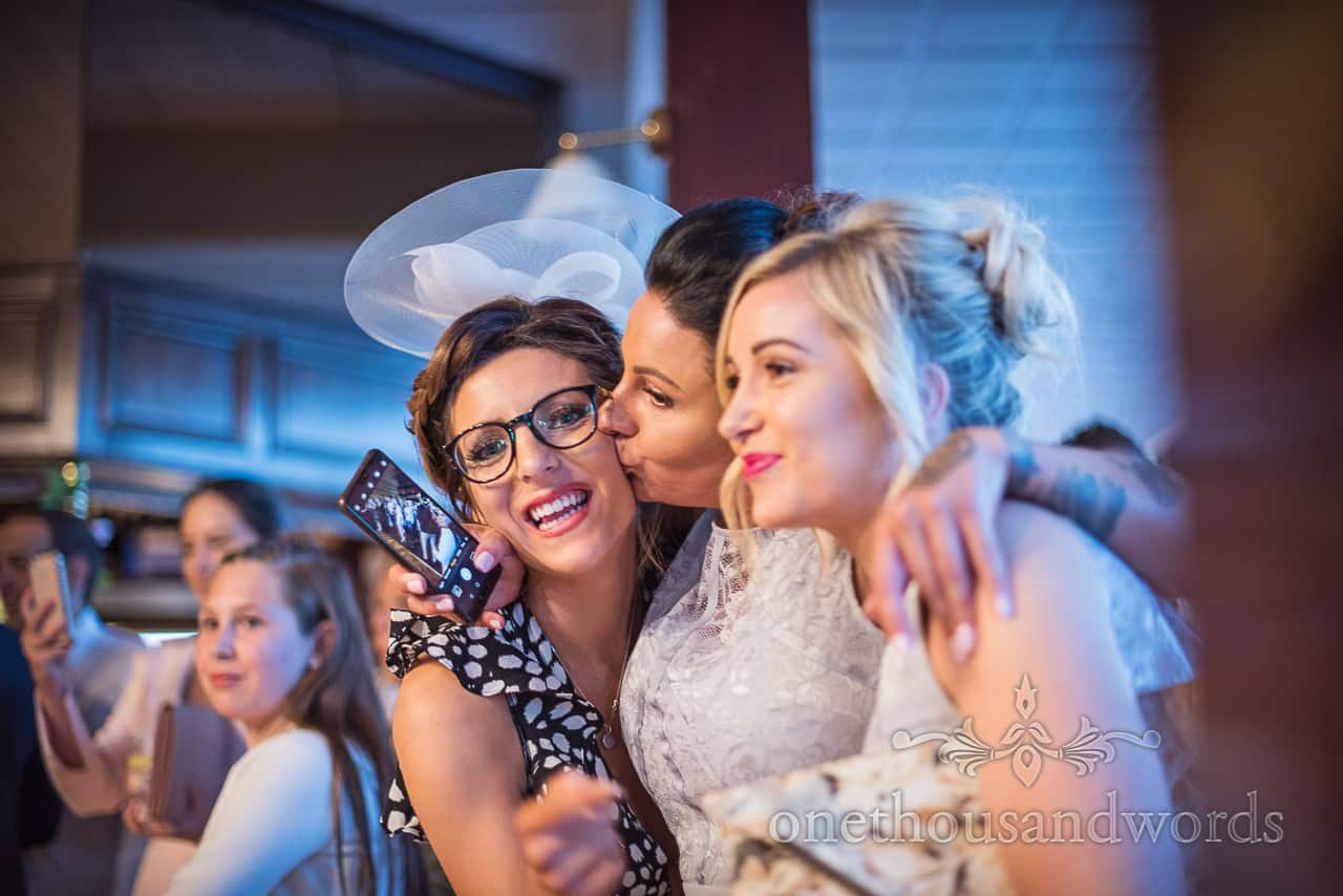 Happy wedding guest with glasses and white hat being kissed on the cheek by a bridesmaid during wedding evening photographs