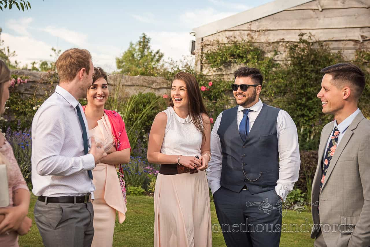 Happy laughing wedding guests photograph at Tithe Barn Dorset garden wedding drinks reception