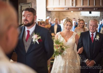 Bride in white wedding dress walked up stone church aisle aisle by father in Dorset village church wedding photograph