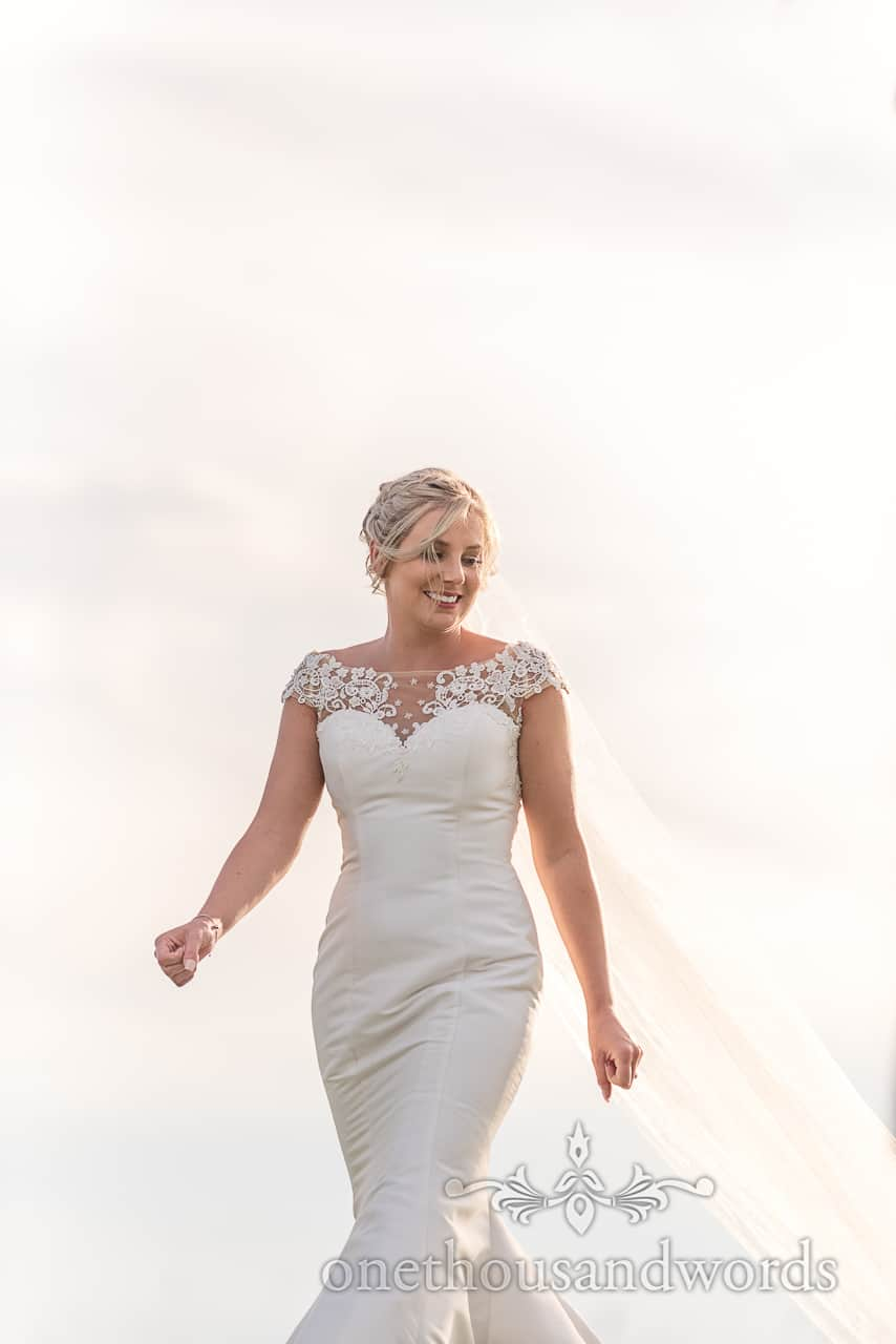 High key natural wedding photograph of smiling bride in bright sunshine wearing a white mermaid wedding dress with lace detail