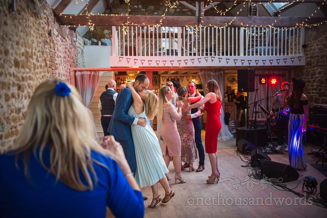Wedding guests kissing whilst dancing at The Tithe Barn Dorset with wedding band evening entertainment