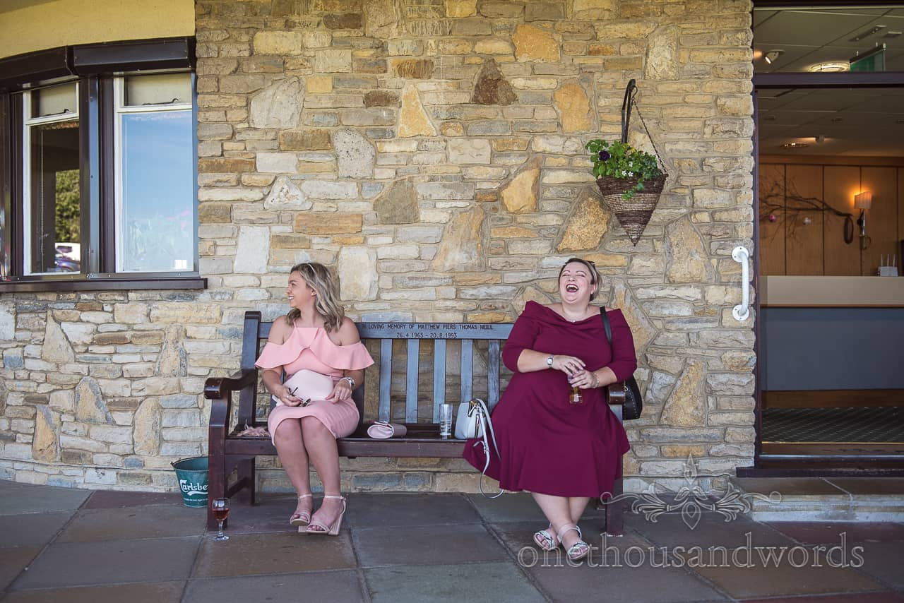 Two female laughing wedding guests sit on a bench at Purbeck Golf Club wedding venue natural documentary wedding photograph