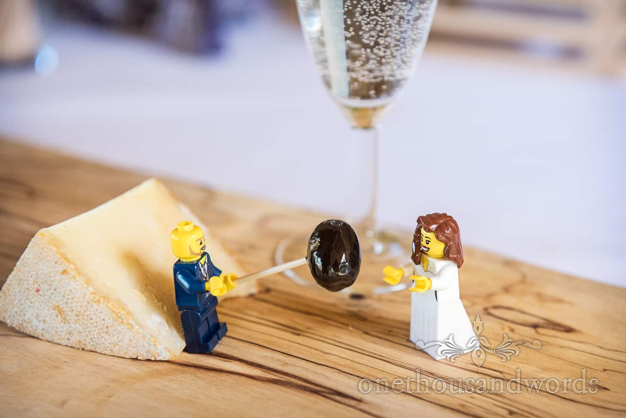 Custom made Lego groom stood with cheese offers Lego bride an olive in macro fun wedding photograph