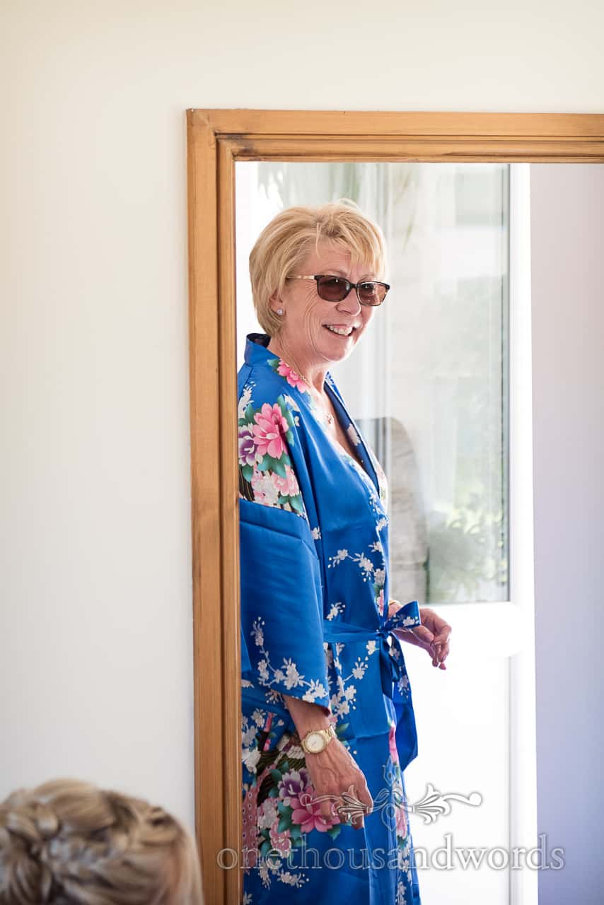 Mother of the bride wearing blue silk peacock dressing gown and sunglasses smiling in doorway during bridal preparation