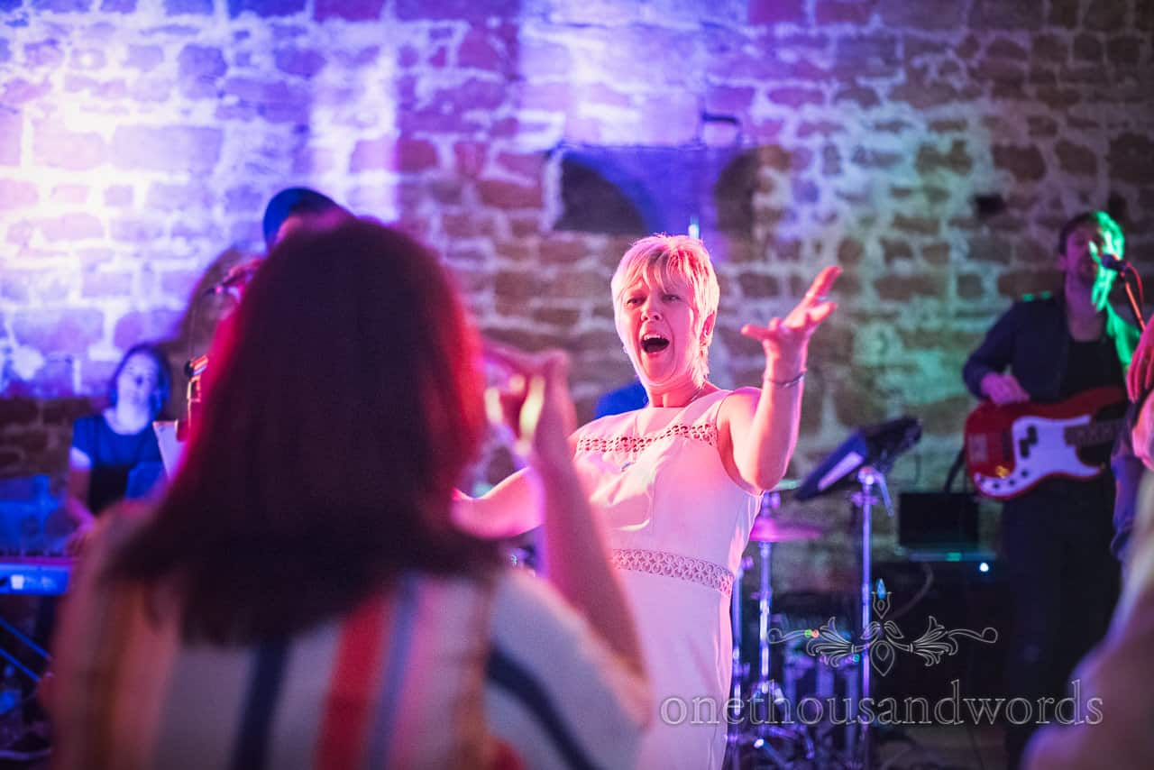 animated mother of the bride singing and dancing under coloured disco lights at wedding evening as wedding band plays in background