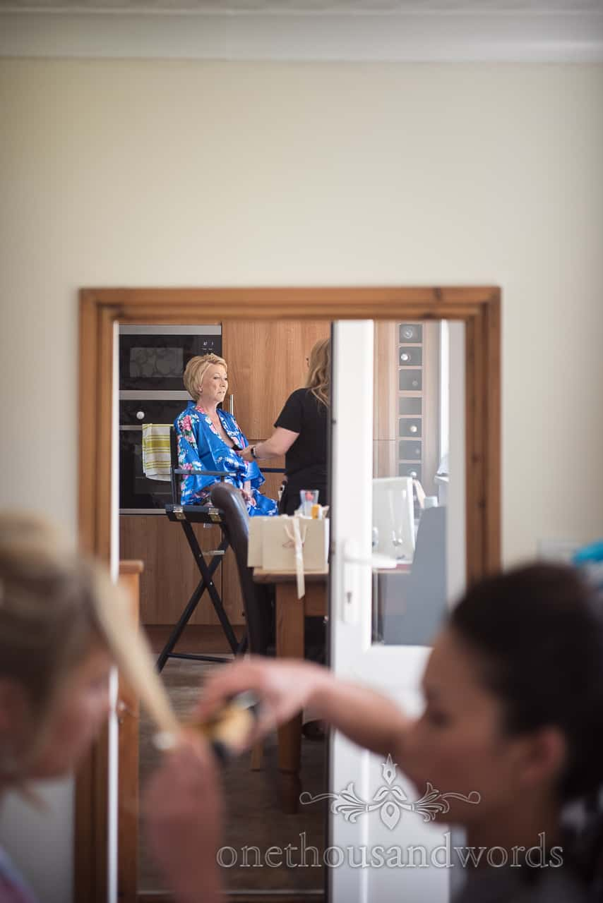 Mother of the bride sits for wedding makeup during bridal preparation photographs visually framed by wooden doorway