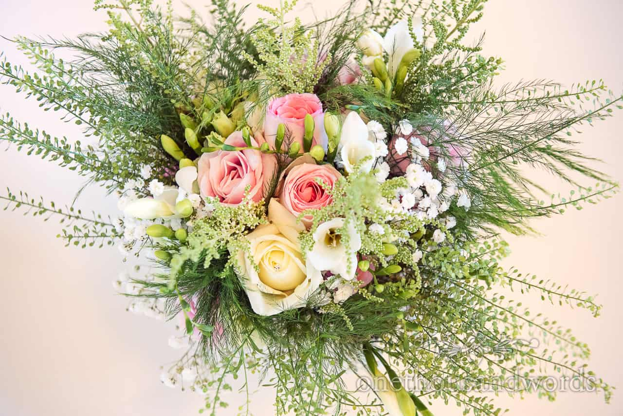 Multicolour floral pink and yellow pastel bridal wedding bouquet with green foliage photograph taken against white backdrop
