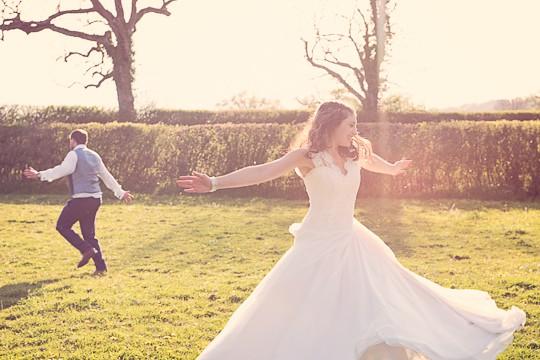 Candid photograph of unaware bride and groom dancing in venue garden