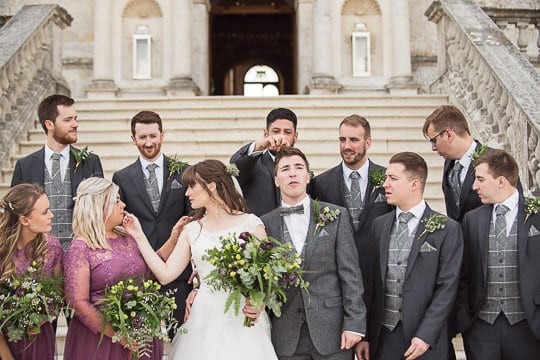 Natural wedding photograph of wedding party before group photographs on stone stairs