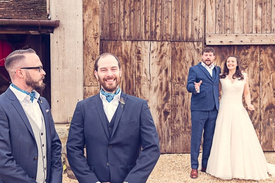 Natural wedding photograph of wedding guests taken during couple photographs outside barn