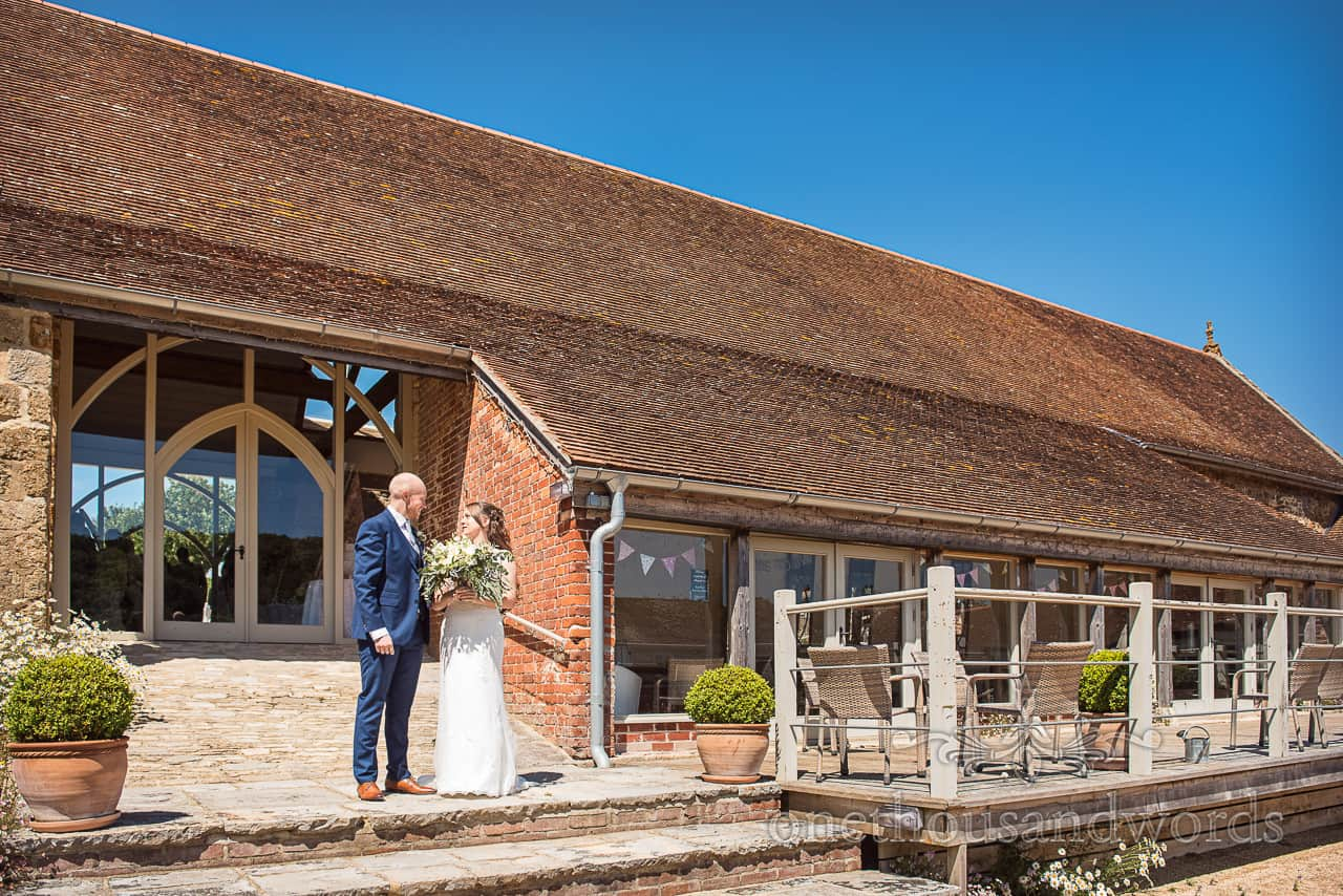 Bride and groom stand outside Tithe Barn Dorset wedding venue in the summer sunshine with blue sky