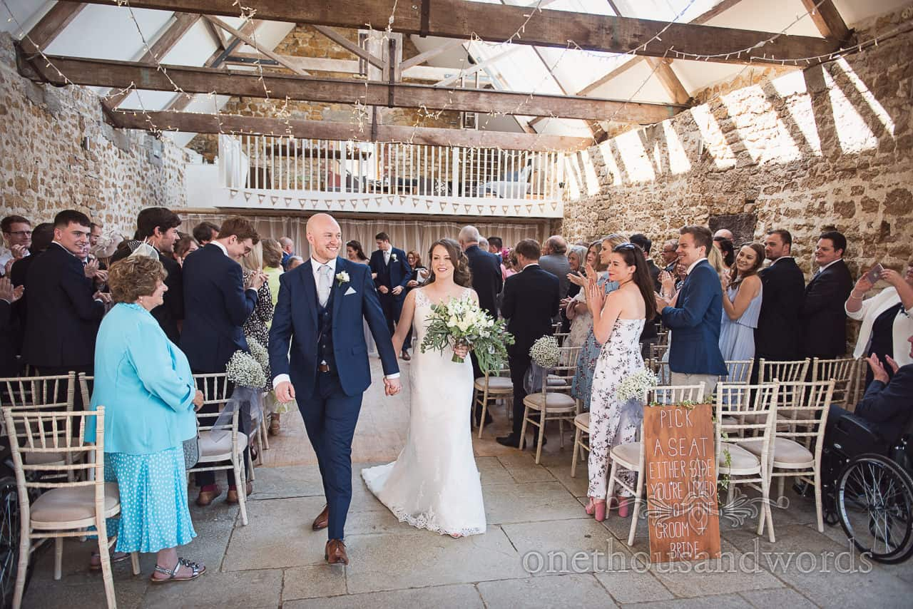 Newly weds walk down the aisle at Tithe Barn Dorset wedding ceremony to standing ovation from wedding guests