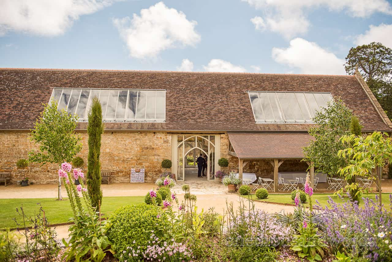 Outside Tithe Barn Dorset wedding venue gardens with summer flowers and blue sky photograph