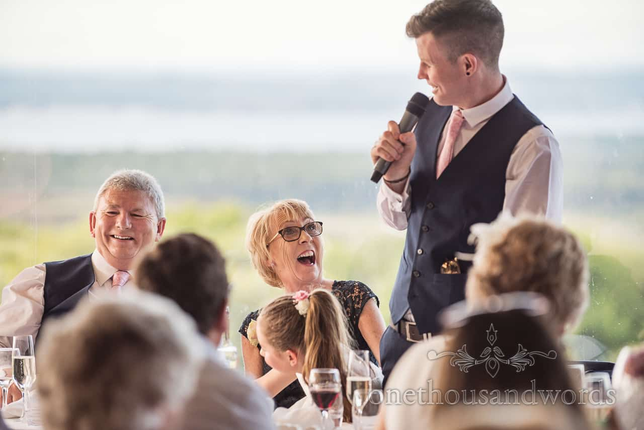 Parents at top table laughing reactions to the grooms wedding speech with microphone documentary wedding photograph