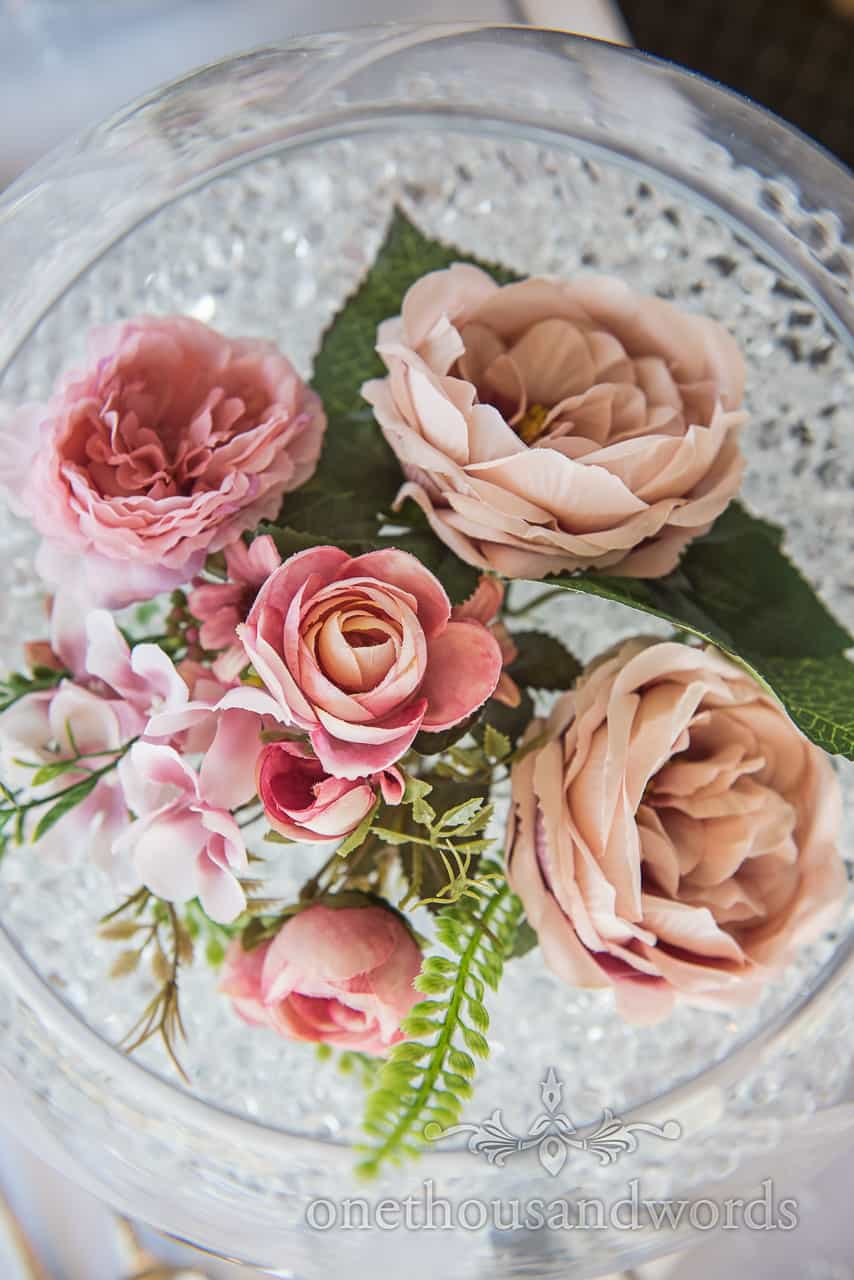Detail wedding photograph of pink linen wedding flower display in round fish bowl filled with crystals wedding table decoration