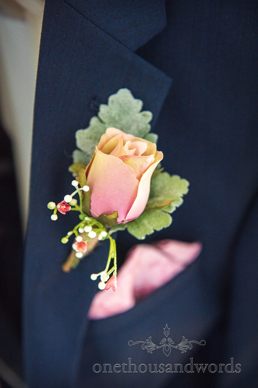 Close up photograph if a pink and yellow wedding buttonhole linen flower pinned into blue wedding suit Lapel