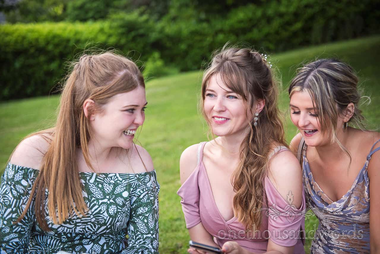 Portrait photograph of beautiful female wedding guests laughing in gardens on grassy hill