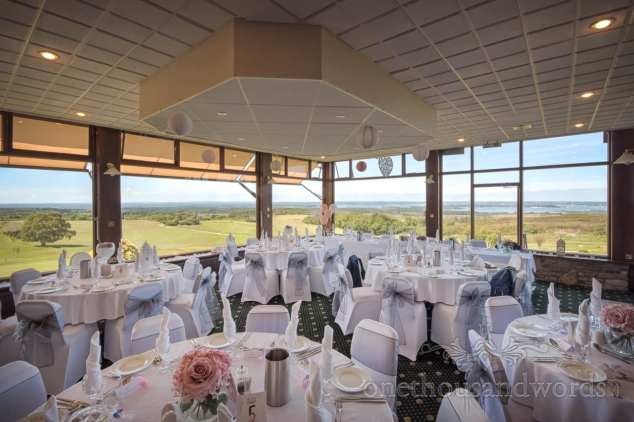 Purbeck Golf Club wedding venue photograph of decorated wedding breakfast room with panoramic windows and countryside views