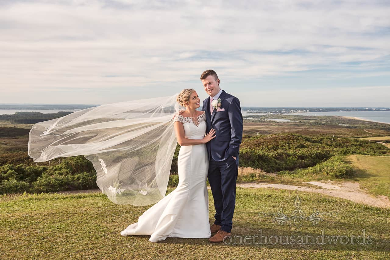 Purbeck Golf Club wedding photograph of bride and groom on golf course with veil blowing in the wind with view over Poole Harbour