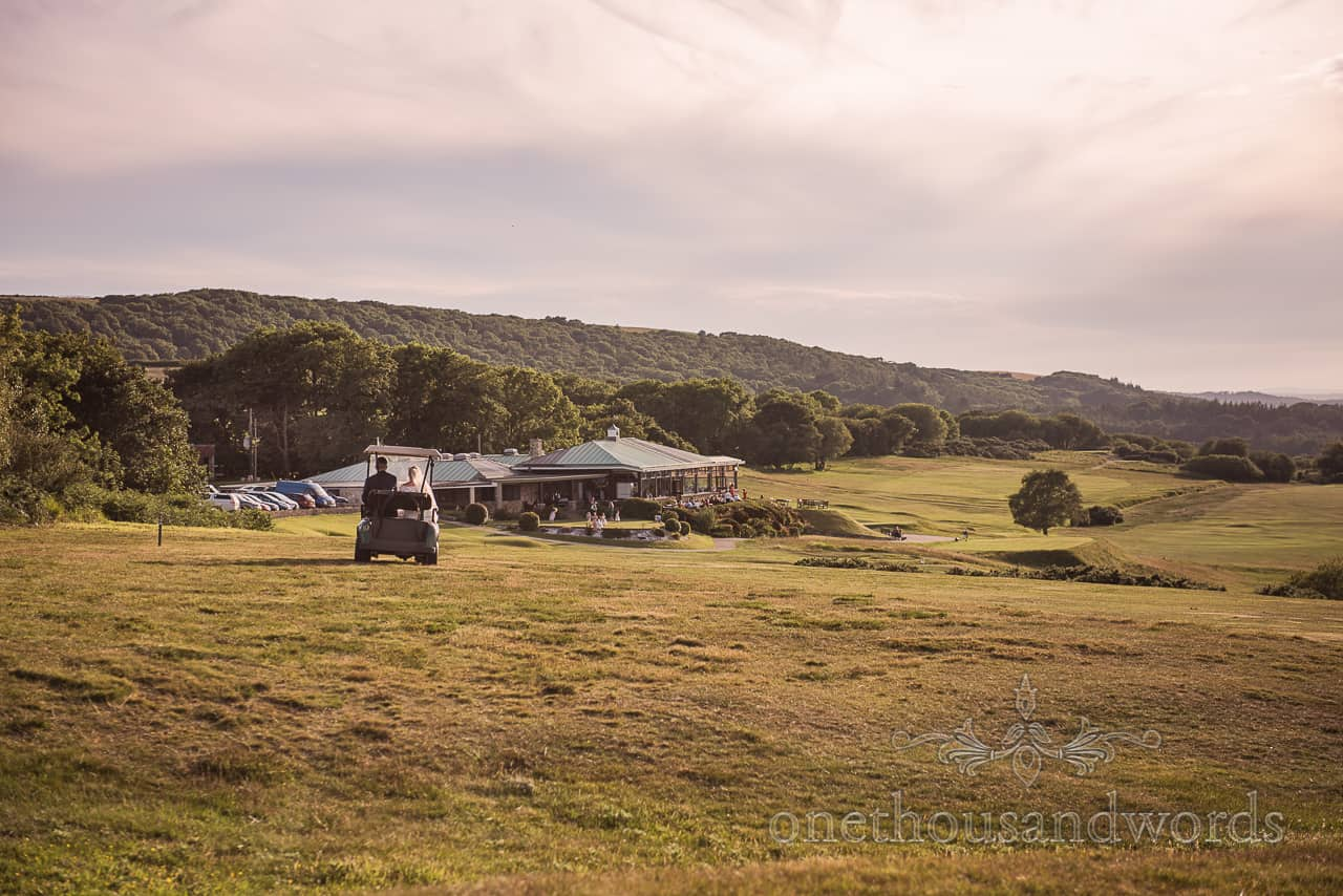 Purbeck Golf Club wedding venue photograph with bride and groom riding across golf course in a golf buggy at dusk