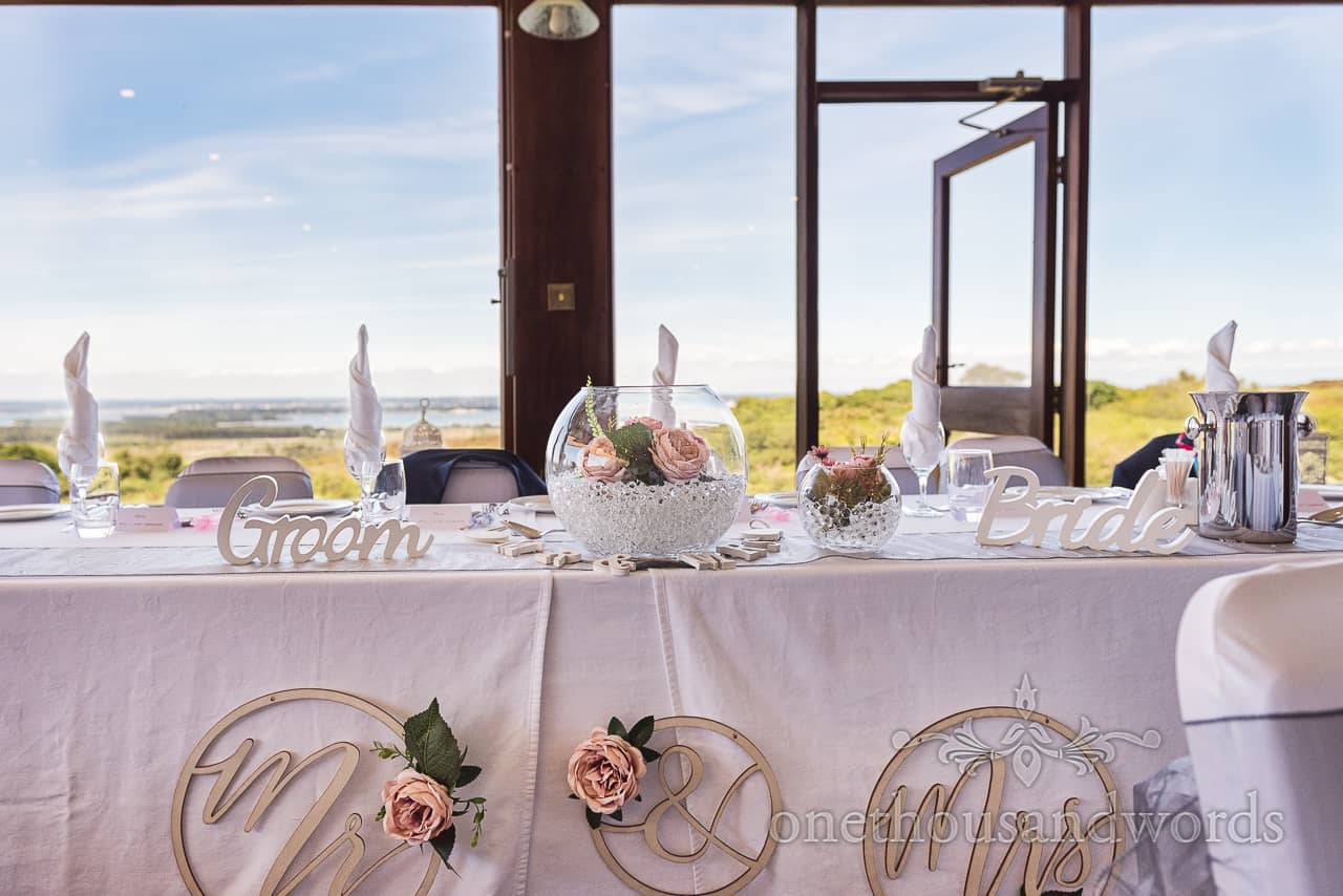 Purbeck Golf Club wedding venue photograph of top table floral and signage decorations with countryside view from window