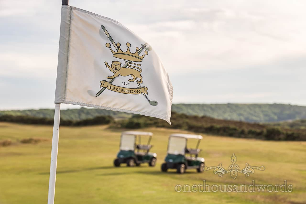 Purbeck Golf Club Dorset wedding venue coat of arms flag or pin with golf carts in the green countryside background